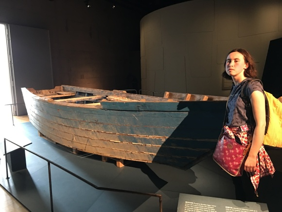 i, a European-presenting woman, am standing beside a weathered wooden boat. the blue paint is pealing off and turning to white.