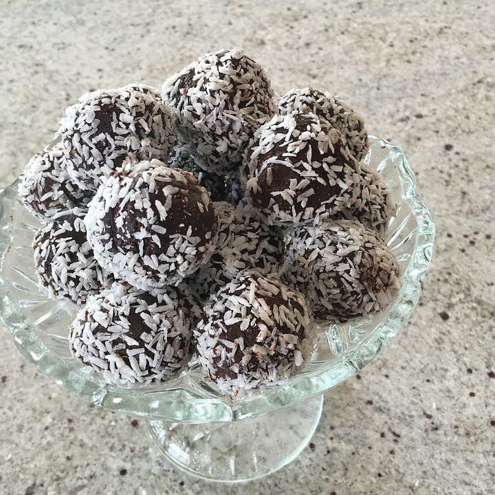 In a bowl, many choklatbollar, coconut-covered chocolate balls are layered.