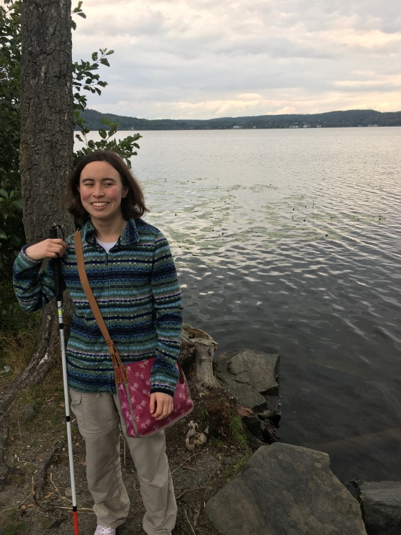 I (áine Kelly-costello) am standing beside a tree in front of a lake. I have a pink handbag on and am holding my cane. I'm a Eurasian white woman with brown hair.