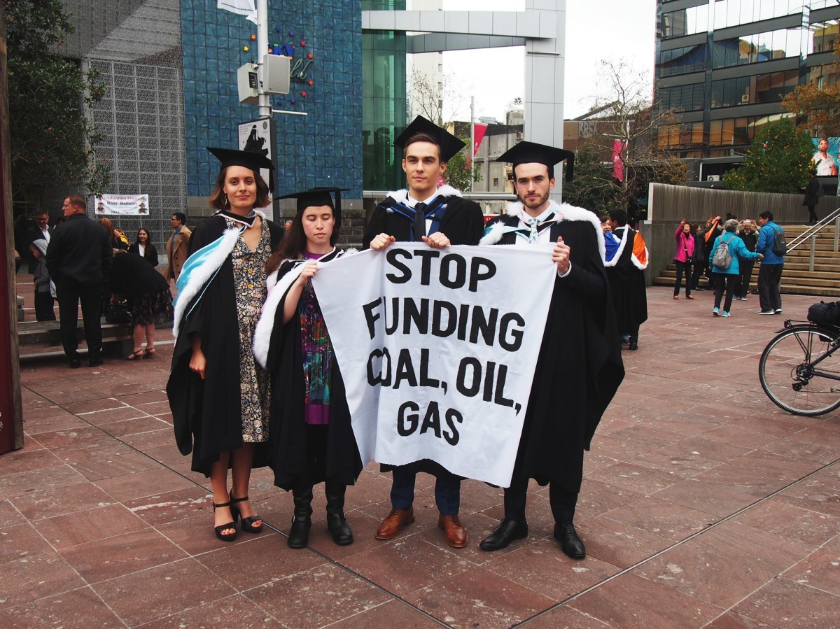 """Four campaigners, including me, in graduation atire, with a sign reading """"Stop funding coal, oil and gas."""""""