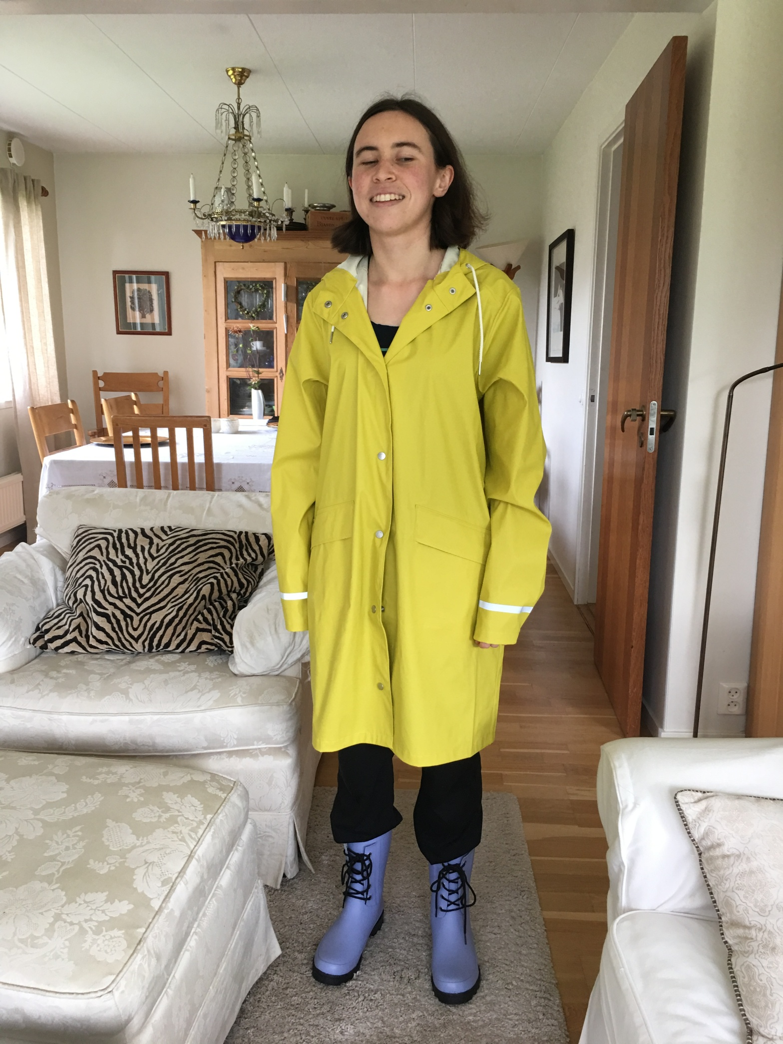 I, a European-presenting female, am standing in a knee-length yellow raincoat and gumboots.