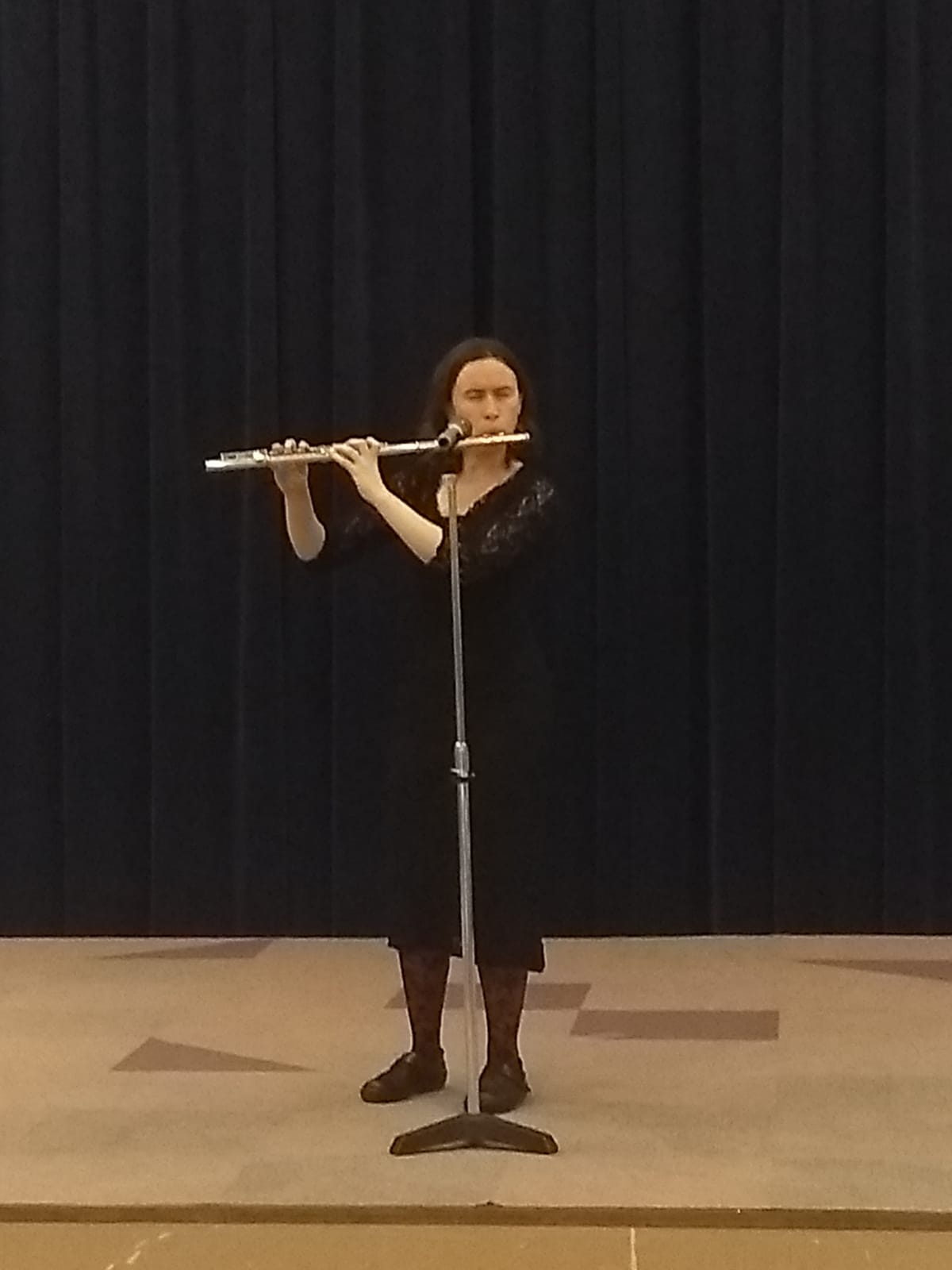 I, a European-presening white woman, am wearing a black dress playing flute. You can see the stage, a microphone I'm playing into, and a black curtain behind me.