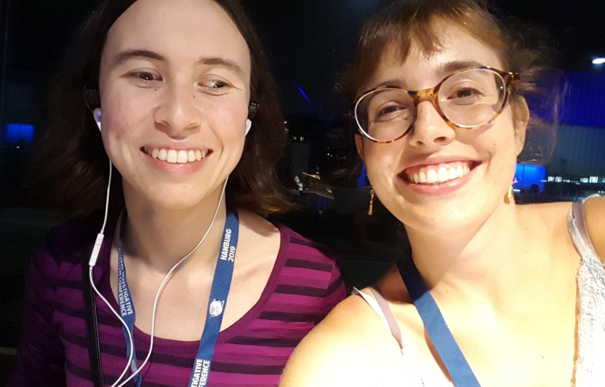 "Two young European-presenting women, Ariadna and I, are sitting at a table smiling. We have blue Conference lanyards on, mine's facing text-side-out and reads ""Hamburg 2019 / Global Investigative Journalism Conference""."