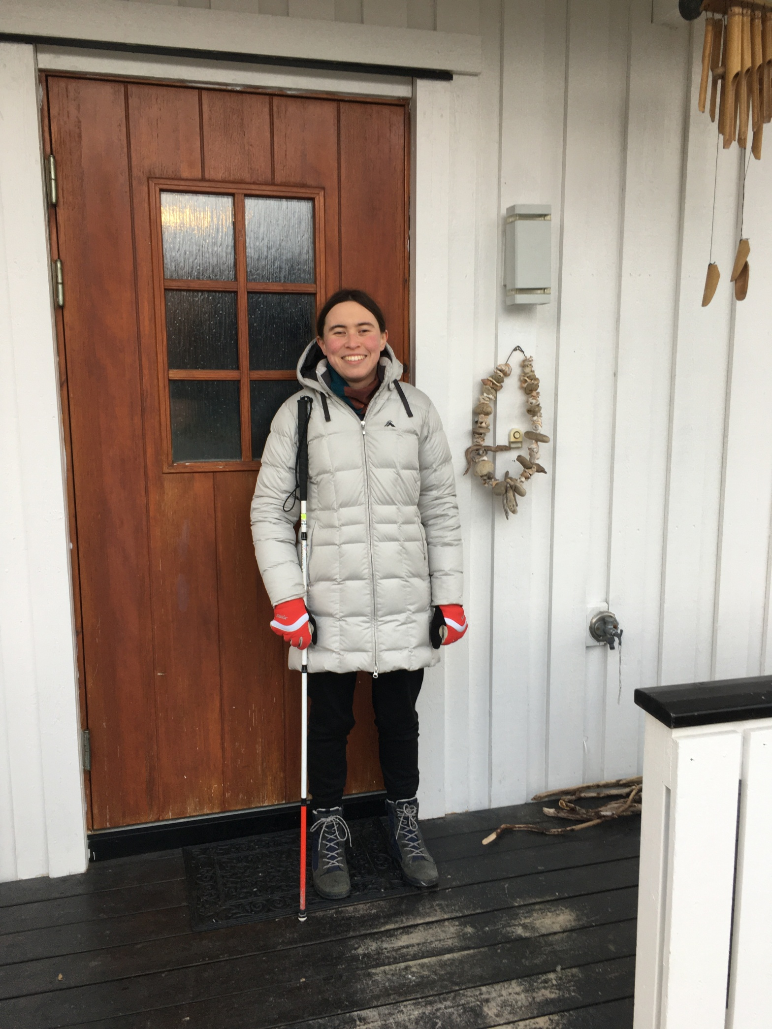 I'm standing bundled up in a winter jacket and scarf outside my new mostly wooden front door, which has a kind of wreath of beach shells and drift wood hanging to my right. I'm a Eurasian-presenting white woman with brown hair.