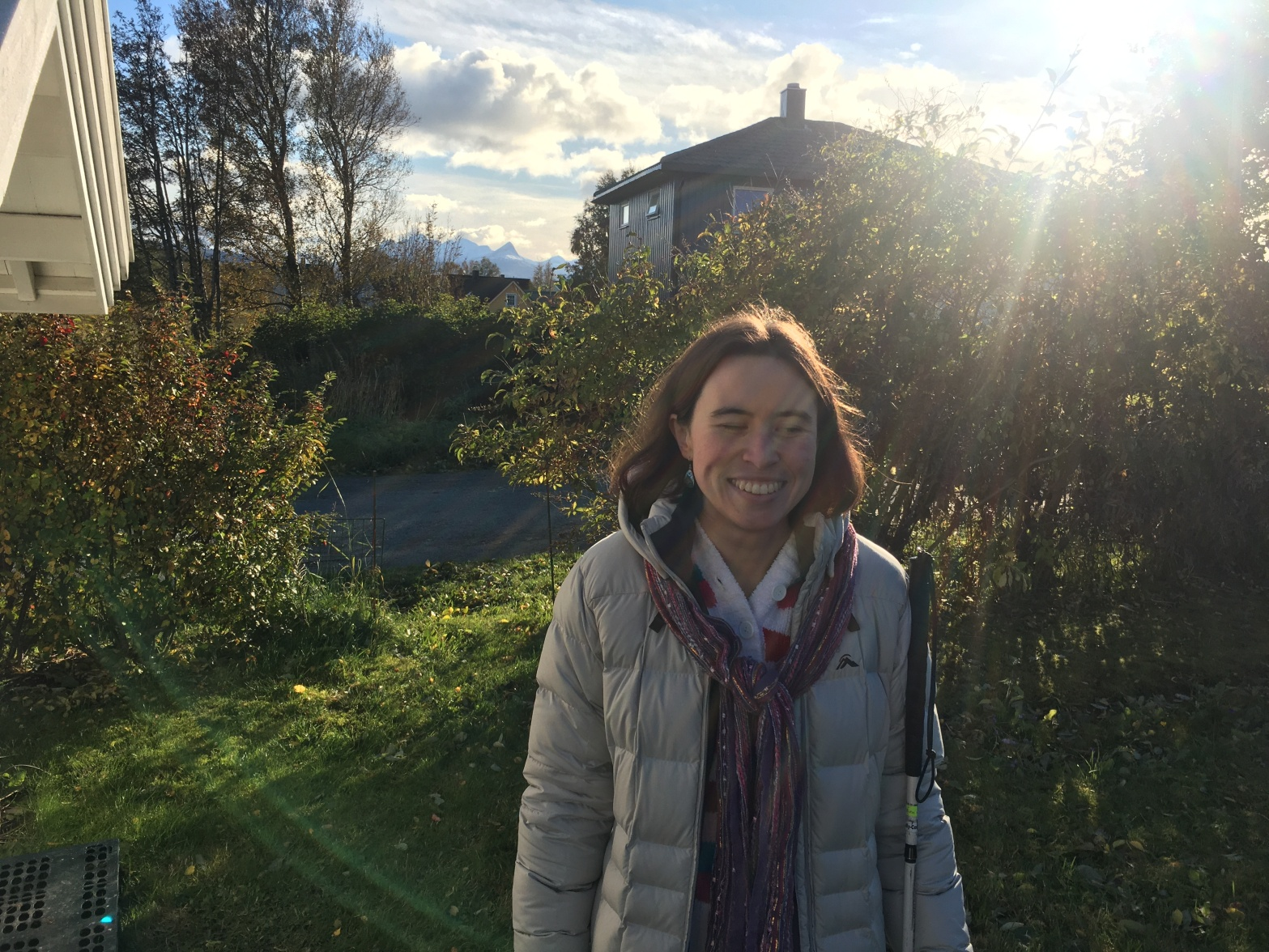 I'm standing on the grass behind my house on an autumn day, and you can see Norwegian mountains behind me. I'm a white woman with brown hair, wearing a puffy winter jacket and multi-colour scarf.